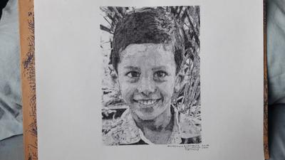 A HANDSOME LITTLE BOY DRAWING WITH BALLPOINT PEN